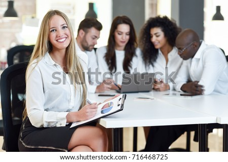 Multi-ethnic group of five businesspeople meeting in a modern office. Caucasian blonde businesswoman leader, wearing white shirt and black skirt, looking at camera. #716468725