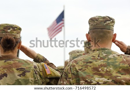 American Soldiers Saluting US Flag Royalty-Free Stock Photo #716498572