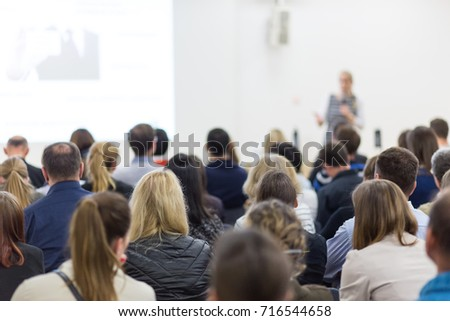 Business and entrepreneurship symposium. Female speaker giving a talk at business meeting. Audience in conference hall. Rear view of unrecognized participant in audience. Copy space on whitescreen. #716544658