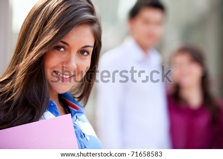 Female student carrying notebooks outdoors and smiling #71658583