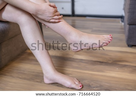 Young woman sitting on the couch suffering from severe pain in the leg. Woman massaging her foot. Pain in calf muscle of the woman  #716664520
