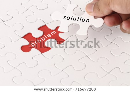 Management concept with hand holding piece of jigsaw puzzle with problem and solution wording Royalty-Free Stock Photo #716697208