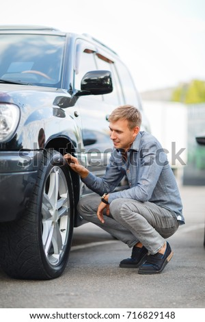 Checking a used car before buying. A man is examining a car. #716829148