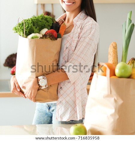 Young woman holding grocery shopping bag with vegetables #716835958