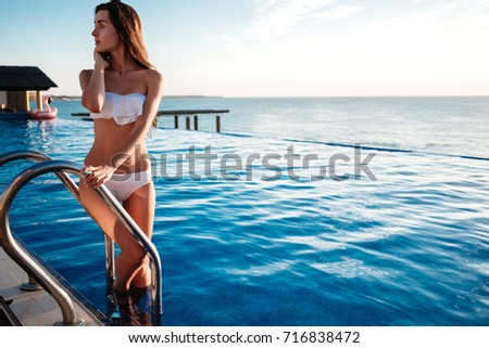 fashion outdoor photo of beautiful sensual woman with long dark curly hair in elegant pink white relaxing beside swimming pool #716838472