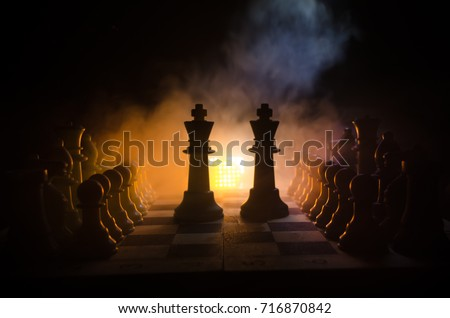 Chess board game concept of business ideas and competition and strategy ideas concep. Chess figures on a dark background with smoke and fog. Selective focus #716870842
