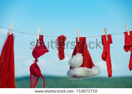 christmas clothes hanging on rope with pin at dry cleaning on blue sky background #716873710