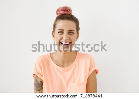 Beautiful euphoric teenage girl wearing her pinkish hair in knot enjoying weekend at home, looking and smiling at camera, her blue eyes full of joy and happiness. People and lifestyle concept #716878441