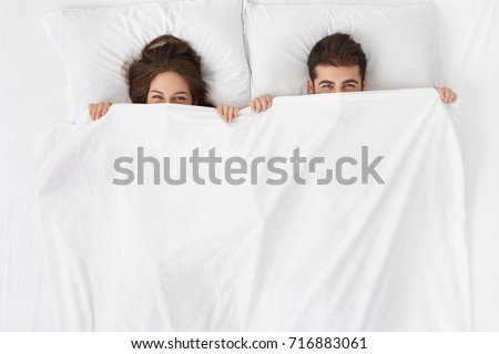Funny married couple lying in bed and hiding under white blanket, looking at camera with eyes full of joy. Attractive Caucasian man and woman having fun in bedroom. Love and happiness concept #716883061
