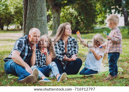 Young family with cheerful children in the park. Bubble blower #716912797