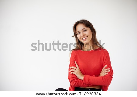 Gorgeous positive young female in black jeans and oversize red long sleeved top wearing her dark hair loose posing in studio, keeping arms folded and looking at camera with joyful cute smile
