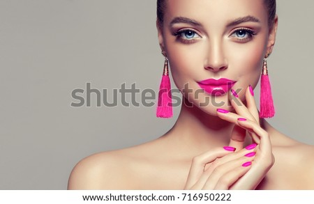 Beautiful model girl with pink fuchsia manicure on nails . Fashion makeup and cosmetics . Large earrings tassels jewelry Magenta color . Royalty-Free Stock Photo #716950222