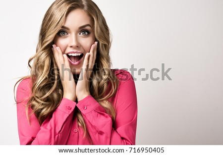 Woman  happy and surprised shouts holds cheeks by hand .Beautiful girl  with curly hair  pointing to looking right . Presenting your product. Expressive facial expressions businesswoman  . Royalty-Free Stock Photo #716950405