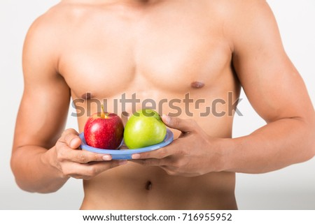 Sportsman Bites Green Apple After Training. Fitness and healthy lifestyle concept. Studio shot on white background. #716955952
