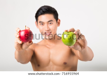 Sportsman Bites Green Apple After Training. Fitness and healthy lifestyle concept. Studio shot on white background. #716955964