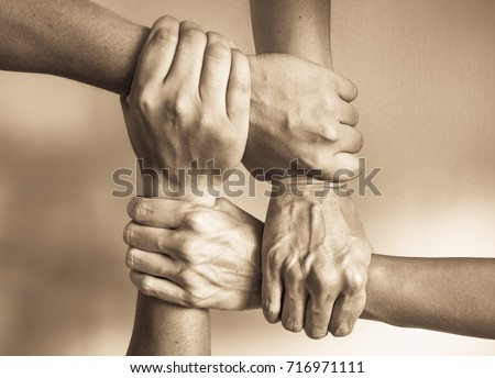 Hands united helping each other. In unity there is strength concept.   Royalty-Free Stock Photo #716971111