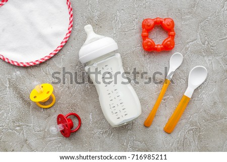 preparation of mixture baby feeding with infant formula powdered milk in bottle, spoon and toys on gray background top view #716985211