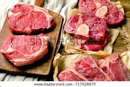 Raw beef meat on a dark wooden board. Top view #717028879
