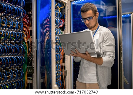 Portrait of modern young man holding laptop standing in server room working with supercomputer in blue light Royalty-Free Stock Photo #717032749