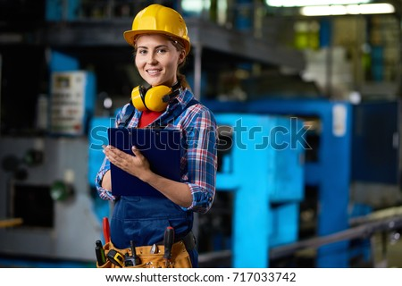 Waist-up portrait of attractive young technician in checked shirt and overall looking at camera with wide smile while carrying out inspection at production department of plant, blurred background #717033742