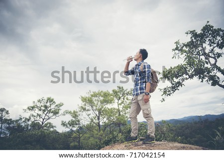 Hiker relaxing on top of the mountain and drinking bottled water #717042154