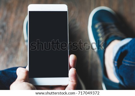 Young man holding a mobile phone. Point of view #717049372