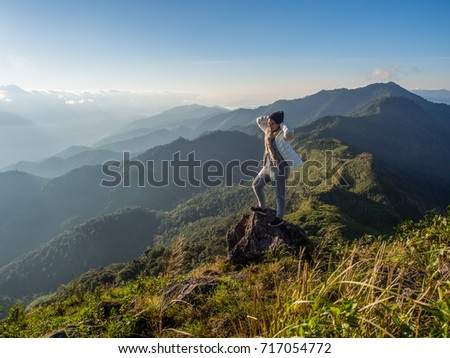 A cool act on the top of green range of mountain ridge with white sunlight shining to the white wind shield of a traveler is a great moment to look at. This great nature is at Doi Phu Wae, Thailand. #717054772