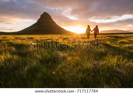 A couple holding hands in a meadow with dramatic sunrise in Iceland. Pre wedding photography shooting. Family love. Young wild and free.