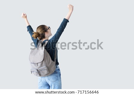 Happy student with arms raised on air Royalty-Free Stock Photo #717156646