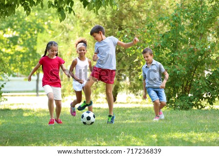 Cute children playing football in park Royalty-Free Stock Photo #717236839