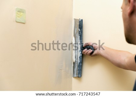 work aligns - worker plastering wall with spatula #717243547