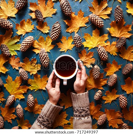 Floral autumn background. A mug of coffee in a woman's hand in a sweater on the green background with yellow falling leaves maple and cones. Hello autumn. Flat lay instagram fashion drink composition. #717249397