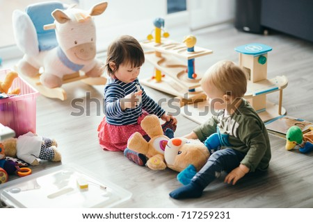 cute little girl and boy playing with toys by the home Royalty-Free Stock Photo #717259231