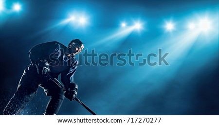 Ice Hockey player is skating on a abstract background with intensional lens flares. He is wearing unbranded sports clothes. #717270277