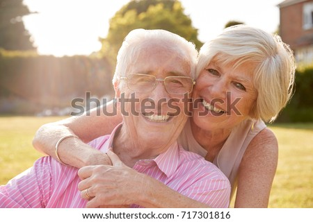 Senior couple in garden, smiling at camera, close up #717301816