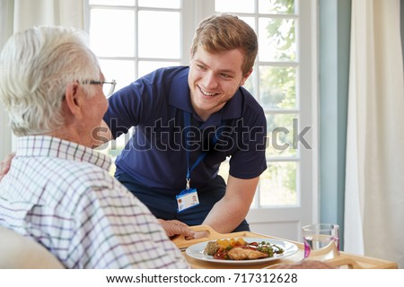 Male care worker serving dinner to a senior man at his home #717312628