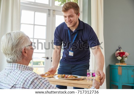 Male care worker serving dinner to a senior man at his home #717312736