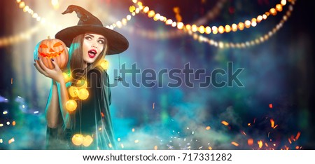 Halloween Witch with a carved Pumpkin and magic lights in a dark forest. Beautiful young surprised woman in witches hat and costume holding pumpkin. Wide Halloween party art design #717331282