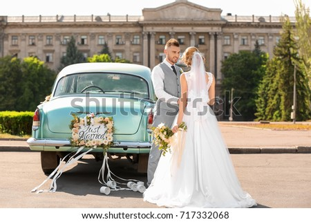 Happy wedding couple near decorated car outdoors #717332068