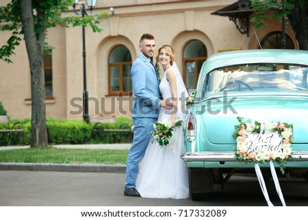 Happy wedding couple near decorated car, outdoors #717332089
