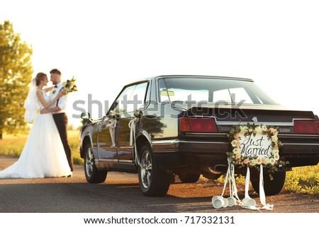 Car with plate JUST MARRIED and happy wedding couple outdoors #717332131