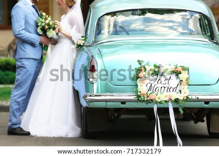 Happy wedding couple near decorated car, outdoors #717332179