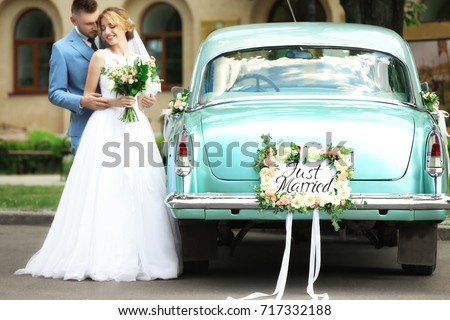 Happy wedding couple near decorated car, outdoors #717332188