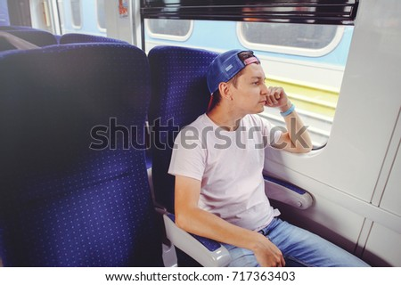 young man rides a train, looks out the window, travel, comfortable trip trip. #717363403