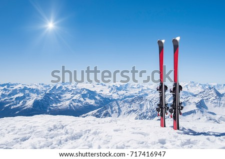 Pair of skis in snow with copy space. Red skis standing in snow with winter mountains in background. Winter holiday vacation and skiing concept.  #717416947