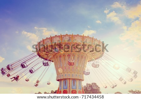 Wave Swinger ride against blue sky, vintage filter effects - a swinging carousel fair ride in amusement park at dusk Royalty-Free Stock Photo #717434458