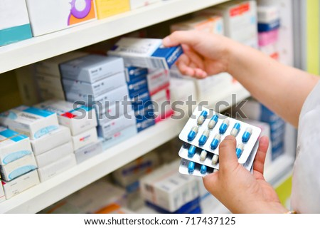 Pharmacist holding medicine box and capsule pack in pharmacy drugstore. Royalty-Free Stock Photo #717437125