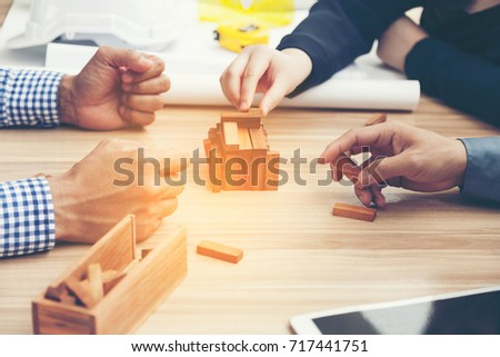 concept young new business man.Close up of hand engineer and architect brainstorming and building wooden jigsaw puzzle together with select focus and use effect filter #717441751