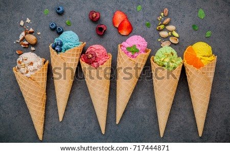Various of ice cream flavor in cones blueberry ,strawberry ,pistachio ,almond ,orange and cherry setup on dark stone background . Summer and Sweet menu concept. #717444871