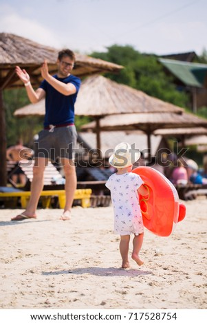 Back view of little boy who walking on the beach and keeping a float in hands #717528754
